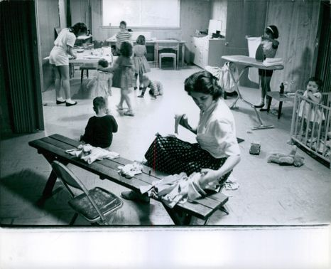 Mother fixing her children's clothes, while the children helps in doing chores.