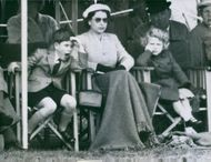 Elizabeth II seated in between her two children, Prince Charles and Princess Anne.