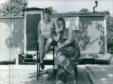 A girl sitting beside the Manne of Klintberg, holding his hands and smiling.