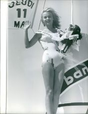 Miss Festival: Cannes, holding a gifts and bouquet, waving, May 15. 1961