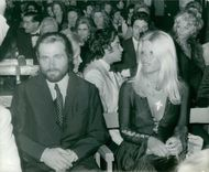 Franco Nero sitting with a woman.