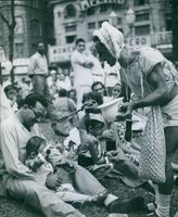 An old man dressed like a baby is giving food to a young boy. 1958