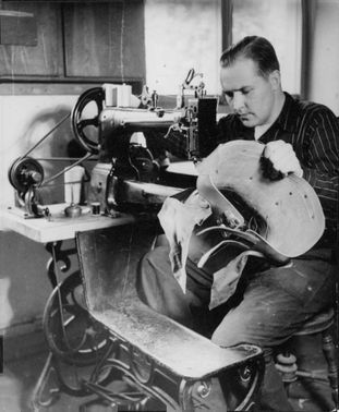 Photo of a man sewing in the sewing machine.