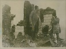 Two men standing at the totally damaged place and talking to each other.