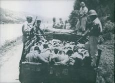 Prisoners being taken to somewhere in truck in the surveillance of soldiers.