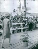 Elizabeth II walks on the docks while people waiting smiled , cheered and waves at her, 1963.