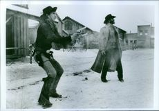 Film Silverado shows Kevin Costner and Kevin Kline both standing and one is holding a gun. 1985.
