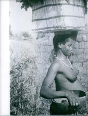 A photo of a naked woman carrying basket on head.  1960