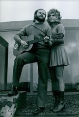 A photo of a  singer duo from Mouscron, Belgium Serge & Christine Ghisoland standing and playing guitar. 1972