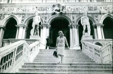 Michelle Morgan descending the stairs looking on her left.