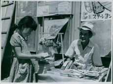 Girl standing at the book stall in street and looking at the books.