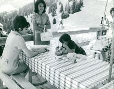 Farah Pahlavi looking affectionately at her daughter.