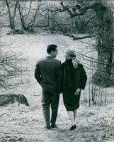 Man and woman in forest, talking to each other while smiling.