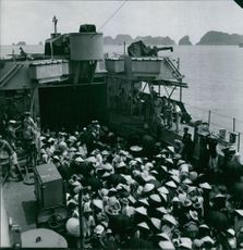 Large number of people wearing wooden hats on a military ship with military men on guard.