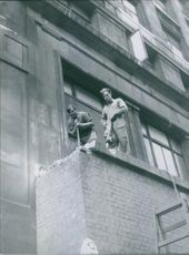 Two men working on the exterior of a building while drilling the concrete in London during the war, 1946.