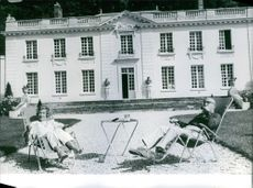 Edgar Faure with his wife sitting on a folding chair outside the house, 1968.