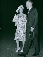 Prince Philip and Elizabeth II walking and talking during one of their travels, 1963.