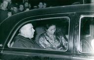 A photo of a man and a woman sitting at the back of the car.