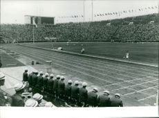 A runner racing in the track field, stadium is full of audience, October 1964.