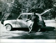 Irina Demich leaning on car.
