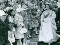 Elizabeth II walking down the stairways while the crowd cheered as she passed them, 1963.