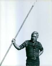 Anthony Quinn standing while holding something.