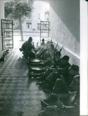 Soldiers are resting in a covered area. 1961