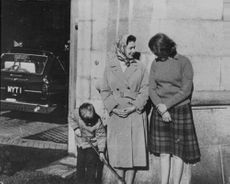 Two women standing on a kerb with a young boy holding a stick