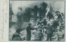 Some men and soldiers getting a dead body from a devastated building during war in England.