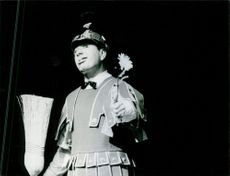 Fernand Raynaud holding a broom and a flower during his performance. 1970.