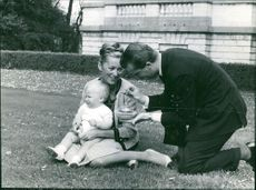 Albert II of Belgium showing a toy to his child.
