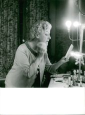 An old woman powdering her face.  - Jul 1964