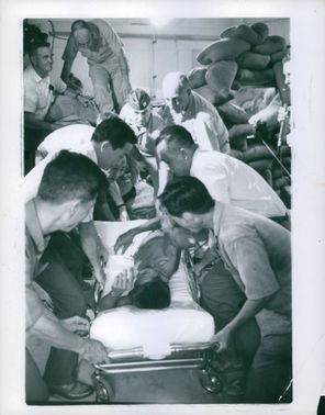 People assisting a man on stretcher.
