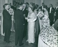 Princess Juliana having a conversation with a man while attending a royal gathering.