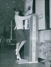 Sherry Young standing and holding a machine, 1961.