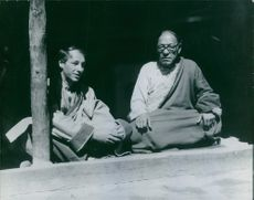 Two men sitting together, looking at something and smiling.