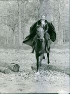 Michel Piccoli wearing a suit with cape and riding a horse.