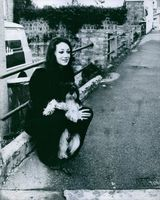 American actress and model Marisa Berenson being photographed with her dog, while she looking at something with smiling face