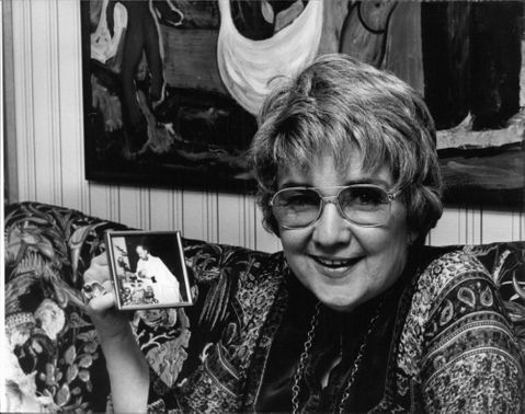 A woman holding a picture frame.