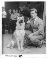Norman Wisdom in a movie scene, talking to a dog.
