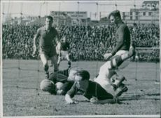 Footballers playing football in the ground, collapsed and spectators watching the match.