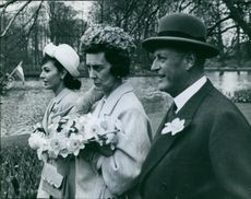 "A photo of Princess Alexandra (left) beside Princess Marina of Kent and King Olav (right) walking while looking to the path.   ""King Olav and Marina of Kent""  1962"