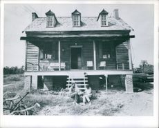 Two kids sitting on the stairs outside of an old house, Travis house.
