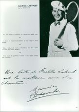 Maurice Chevalier holding racket and smiling.