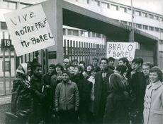 People gather during a rally and holding up signs with Jacques Borel's name written on it. Photo taken on 1965