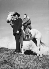 Two children riding on horse, Sigge Furst holding bridle.