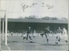Footballers playing match in the ground and spectators watching.