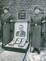 Two soldiers standing beside memorial of a man.
