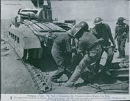 Soldiers salvaging a tank.