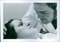 Man talking and looking at her wife, lying in hospital.